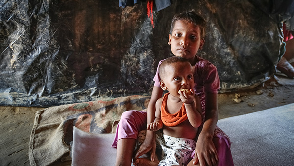 child with younger sibling sitting down inside a makeshift shelter ©Turjoy Chowdhury/Disasters Emergency Committee