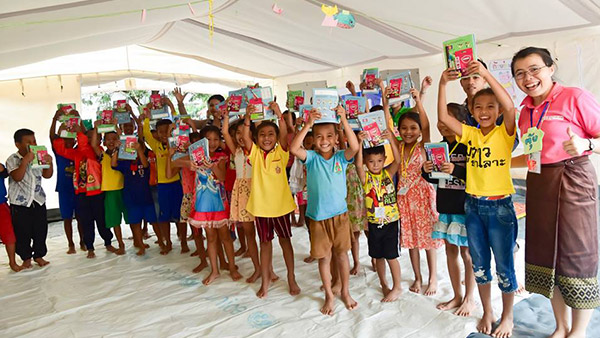 Children receiving learning materials ©Plan International