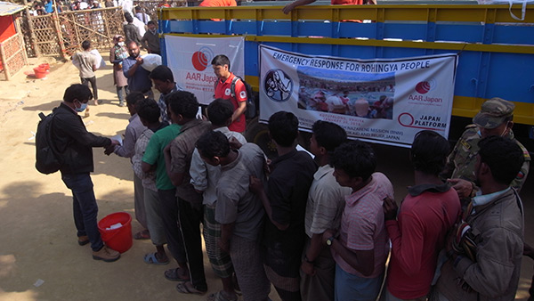 Refugees queuing for the distribution of relief items at the distribution point in Kutuparon refugee camp. The one in the middle with red t-shirt is Fukuro Kakizawa from AAR Japan/ January, 2018/ Kutuparon Refugee Camp ©AAR