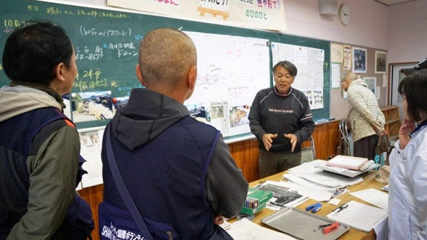 Staff from SVA, a JPF member NGO, listening about the extent of the damage from people at Saku Shiritsu Aonuma Elementary School which is serving as an evacuation center ©SVA