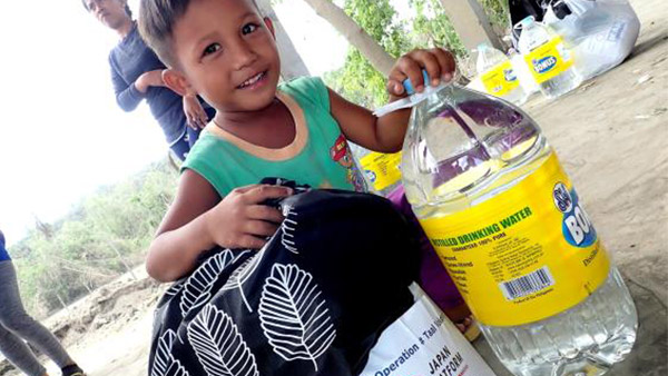 Child smiling after receiving food ©ICAN
