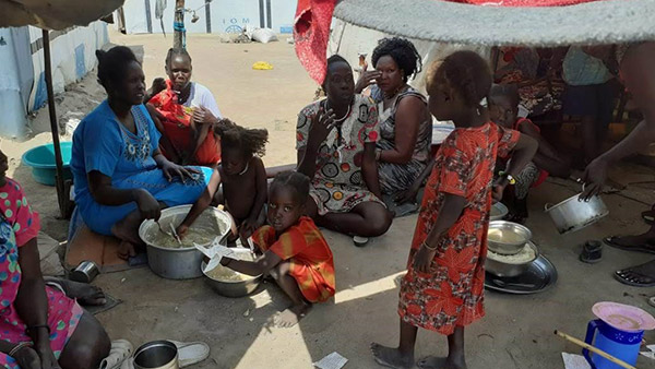Residents cooking outside their tent at IDP camp ©REALs