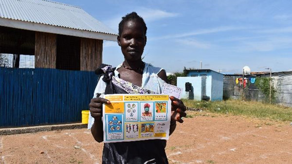 A beneficiary woman receiving the leaflet ©REALs