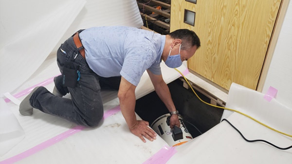 Setting up a blower under the floorboards ©Vnet