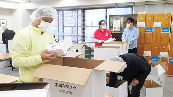 Sheltered workshop workers carefully checking boxed masks and packing them into cardboard boxes ©AAR