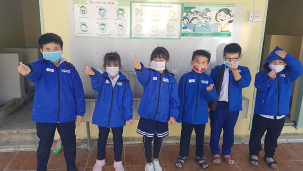 Children looking very happy; they're wearing jackets with JPF and PLAN logos ©PLAN