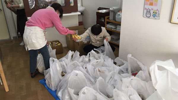 Volunteers help prepare food packages ©PARCIC