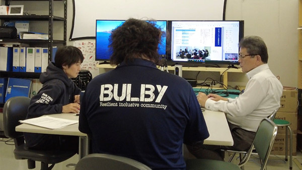 """Creating the booklet """"Mifunet: A Record of the Mifune-town Disaster Support Group Network,"""" which summarizes the lessons learned from the collaborative disaster support meetings in Mifune-town ©BULBY"""