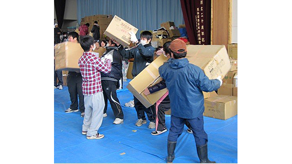 Photo [©PWJ]: Bringing relief items into the gymnasium serving as an evacuation shelter