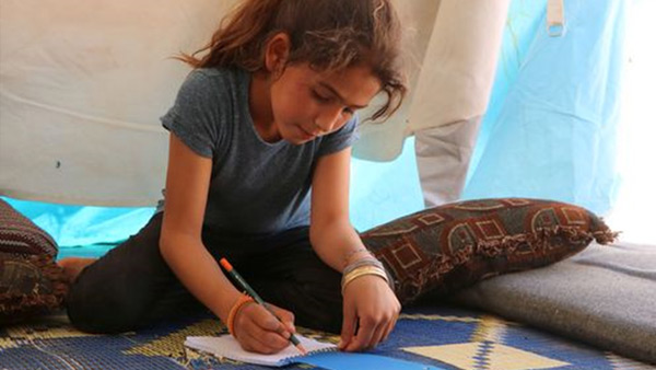 A Syrian child studies in her tent where she is taking shelter from the conflict ©WVJ